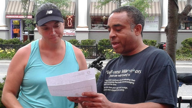 Bill Hill goes over the route map with Tracy Bragiel of Livonia.