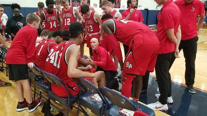 Longtime St. Andrew's coach John O'Connell, center kneeling, talks to his team during a timeout Tuesday. The Scots beat Westminster Academy 70-61 to advance to the Class 3A-Region 3 final Friday.