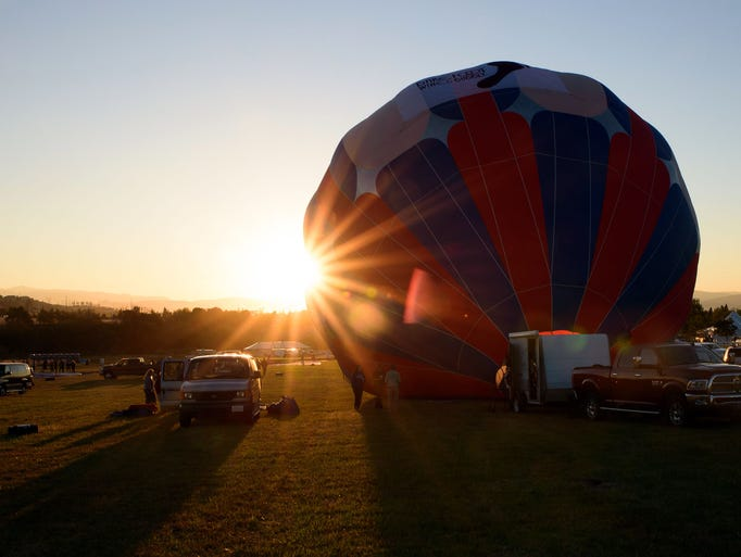 The first balloon begins inflation at the Reno Balloon