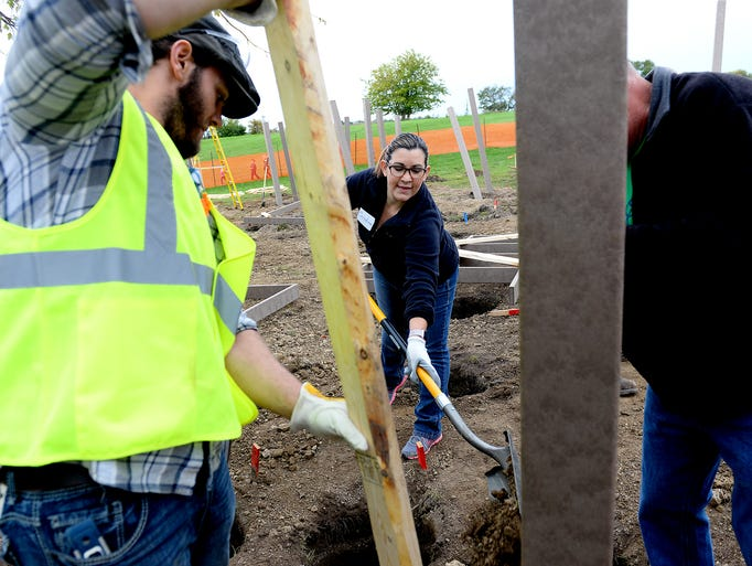 Cristy Dowker tosses dirt into a hole to steady a post
