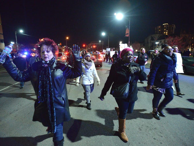 Demonstrators march through traffic on Warren during