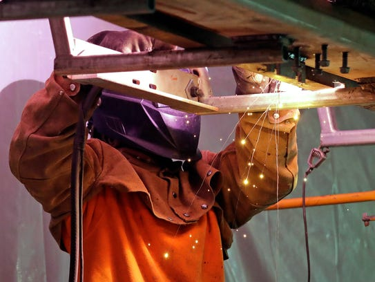 A welder works on the viewing platform atop the Space