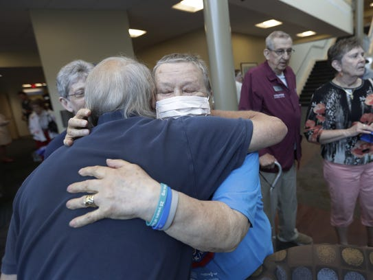 Patients Paul Horvath, left, of Appleton and Willy Schumacher of Kaukauna embrace during Wednesday's Ring that Bell event at Fox Valley Hematology & Oncology in Appleton. Schumacher also is a volunteer.
