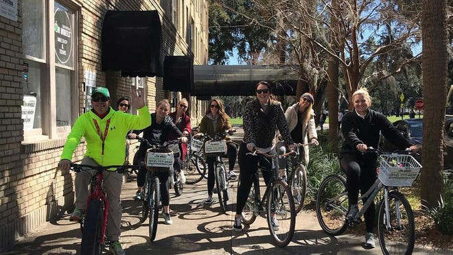 Savannah on Wheels tour guide Daniel Hunter, front left, gets ready to lead a bike tour in March.