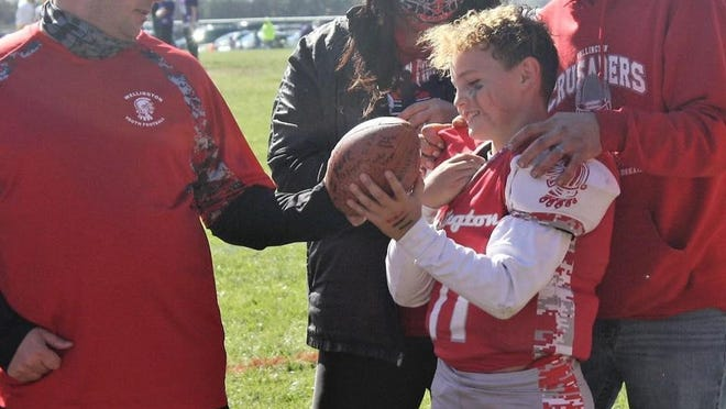 From left, Coach Brandon Lambert hands Colton Elmore the game ball. Behind him are his parents, Jaime and Justin Elmore.