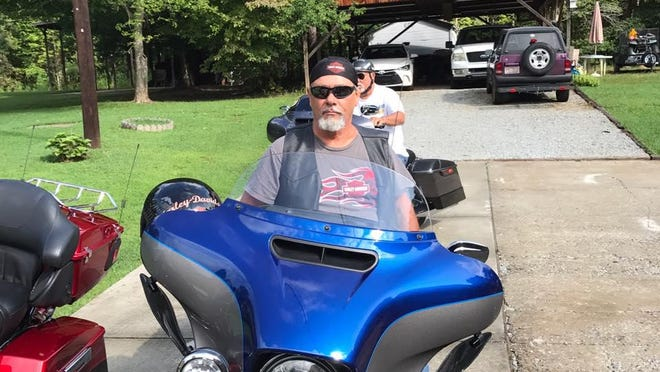 Johnny Frazier is seen in the forefront on his Harley-Davidson motorcycle.