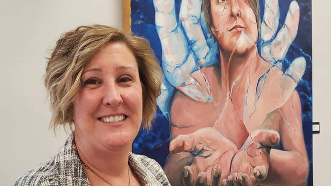 """Lenawee County art educator Taina Mantey, a longtime member artist of the Adrian Center for the Arts, stands next to her oil painting """"giving UP."""" It was one of 92 pieces selected for the National Art Education Association's virtual show for 2020-21."""