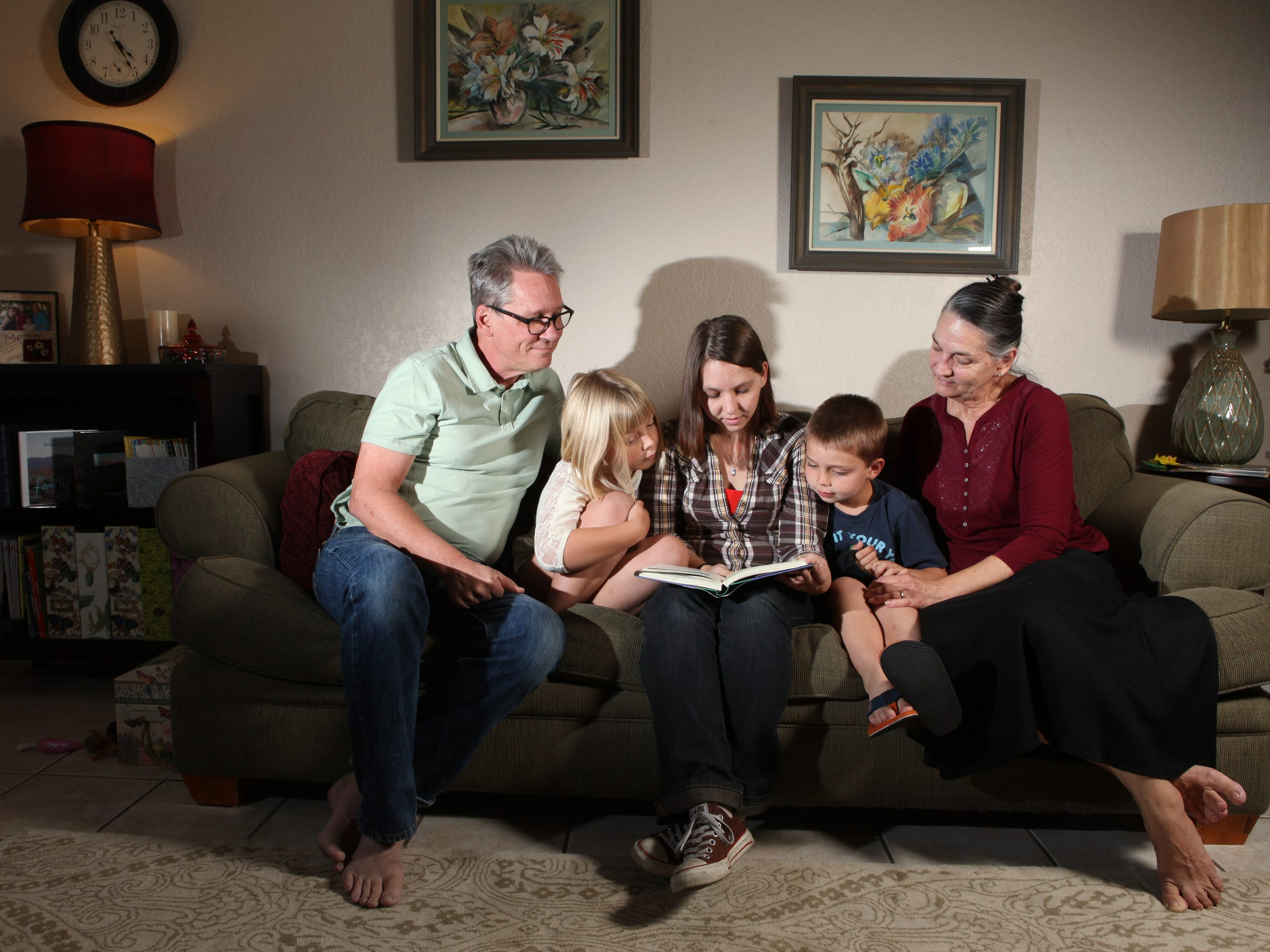 The McKay Family: (From left) Robert, 59, Lily, 8, Hilary, 32, Milo, 6, and Colleen, 59, read together as a family.  As a multigenerational family, Hilary often brings her children to their grandparents' home which is located just down the street from her home.