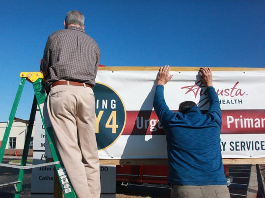 Bob Kasonik of R.E. Lee and Sons construction, right, and Dave Fiero, Augusta Health construction manager, hang the grand opening sign Saturday for Augusta Health's new urgent care center in Stuarts Draft, ready to receive patients May 4.