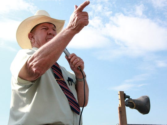 Veteran auctioneer Henry Curd coaxes a higher bid from the crowd on hand in Fishersville Saturday where a house built by Valley Career and Technical Center students ultimately sold for $51,000.