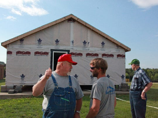 Former Valley Career and Technical Center carpentry instructor Kenny Hodges talks with alumnus Jacob Peters about this year's student-built project, a three-bedroom, two-bath home that was auctioned off in Fishersville Saturday for $51,000.