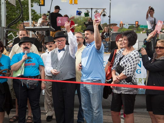 Members of the St. George community, including St. George Mayor Jon Pike in light blue shirt, commemorate the first George Streetfest on Friday, June 5, 2015.