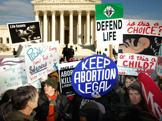 Anti-abortion and pro-choice demonstrators argue in