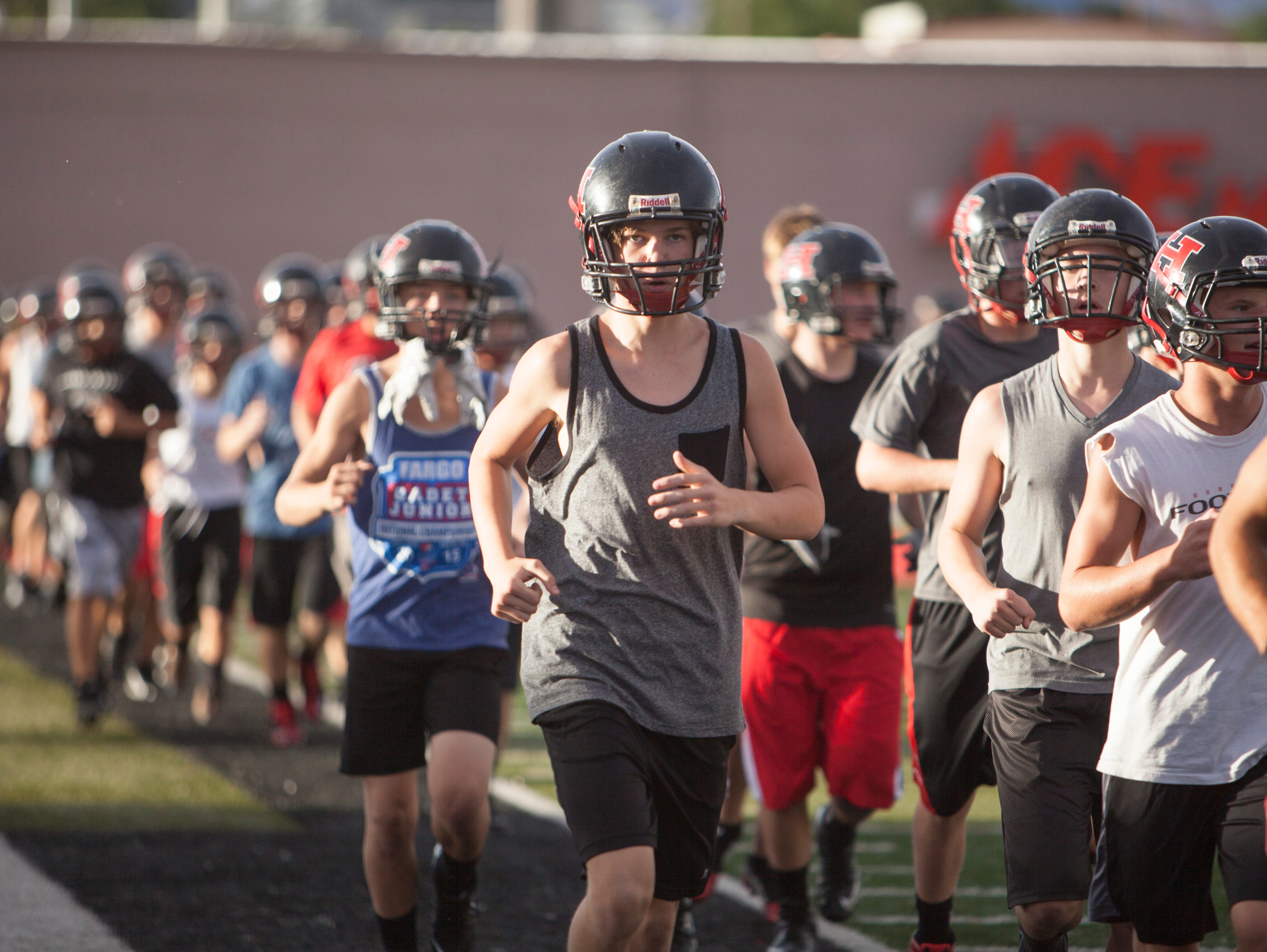 Members of the Hurricane High School football team practice in the final weeks before the start of the season Friday, Aug. 7, 2015.