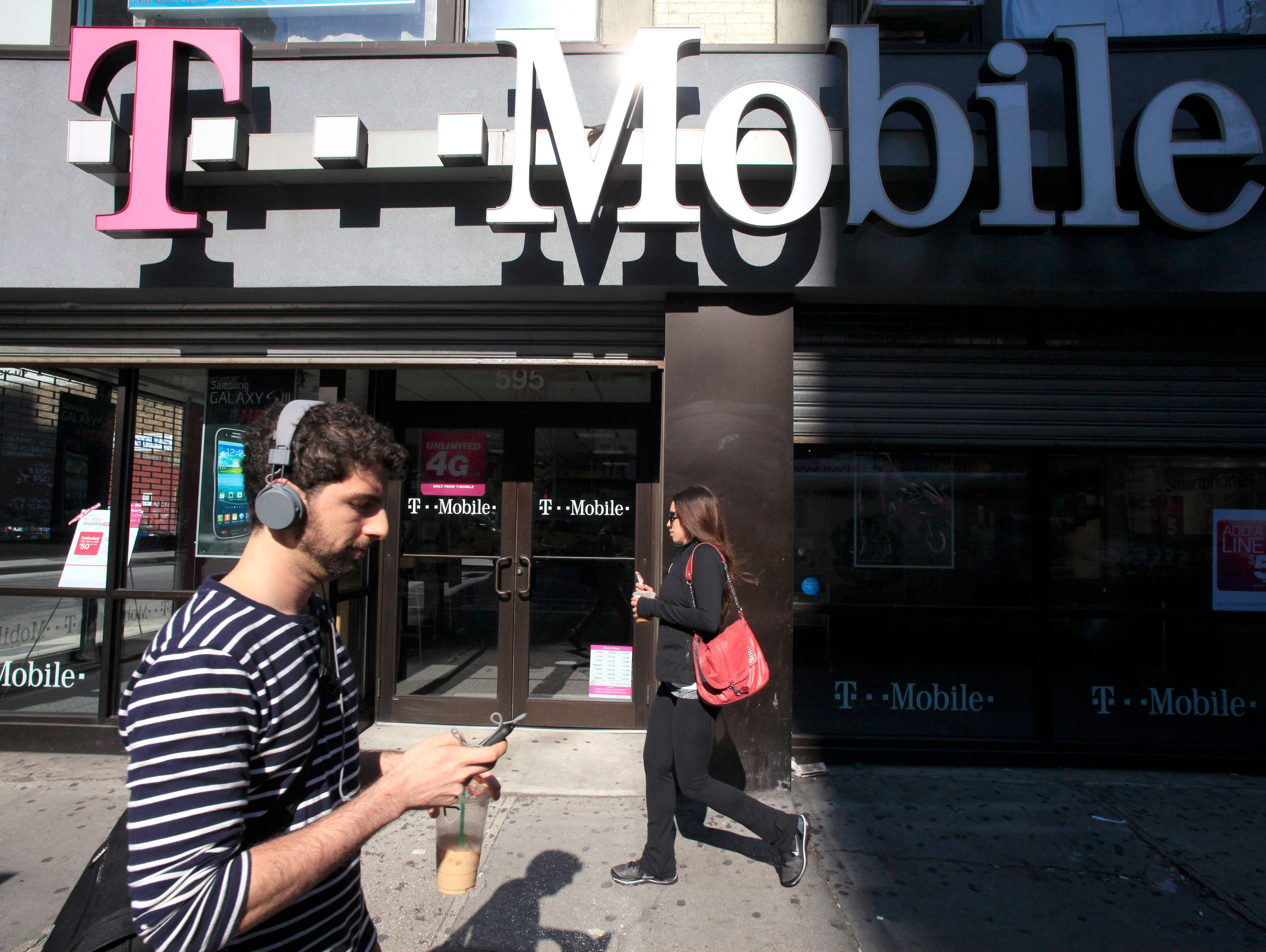 In this Sept. 12, 2012 file photo, a man uses a cellphone as he passes a T-Mobile store in New York. Credit reporting agency Experian on Thursday, Oct. 1, 2015 said that hackers accessed the social security numbers, birthdates and other personal info