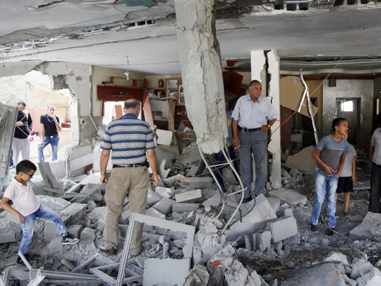 Palestinians inspect the home of the Abu Jaber family