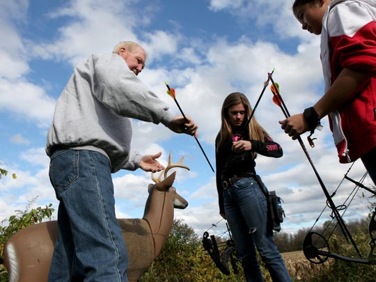 Steve Vanzile, who teaches youth bow hunting and archery, retrieves  arrows with Samantha Sorokti , 14,  and Kayla Bartkowski, 13.