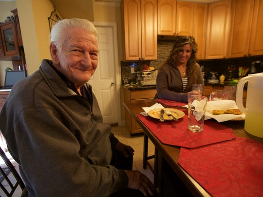 Mr. Ben sits with Wendy Machado after enjoying fried green tomatoes at Theresa Froumy's house.