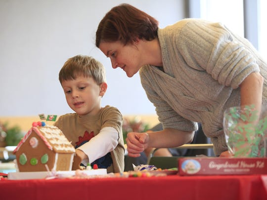 Brogan Long, 6, works with his mom, Amy Long, on their gingerbread house at a Minnetrista-hosted gingerbread family workshop.