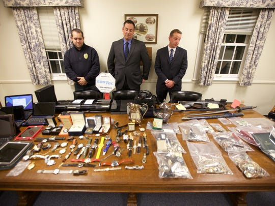 Detectives involved in the case stand near a pile of stolen goods. From left to right: Ocean Township Detective Jeffrey Malone, Little Silver Police Detective Gregory Oliva, Shrewsbury Borough Police Detective Sgt. James Ramsey