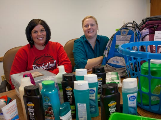 Heather Robinson-Moore, who started the College Baskets Program, and Sunshine Ratliff, who currently runs the program, pose in front of donated items Thursday, Jan. 14, 2016 at St. Clair County Department of Human Services. The program sends supplies to area foster youth that are now attending college.
