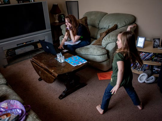 "Kristen Suratt, 22, works on a Spanish course on her computer while her daughter Aurora, 4, dances and sings ""watch me whip,"" Thursday, Jan. 14, 2016 at their Port Huron home. Suratt is going through the Michigan Works Young Professionals program to receive her high school diploma. After finishing her diploma, Suratt plans to pursue a a degree in health care."