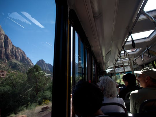 Zion National Park visitors watch the park's red sandstone