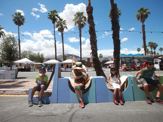 """The Abbasi family enjoy trying out the """"street chairs"""" at the Vision San Pablo street fair in Palm Desert on May 7, where the city demonstrated some changes it wants to make to the street under the General Plan update."""