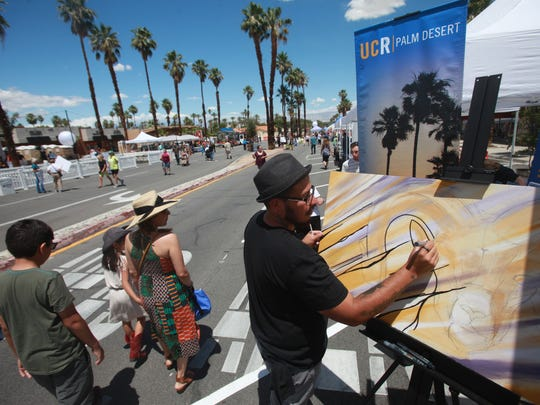 """Artist Enrique Rodriguez does """"live art"""" at the Vision San Pablo street fair in Palm Desert on May 7, 2016. San Pablo Avenue improvements are scheduled to start in the summer of 2018."""