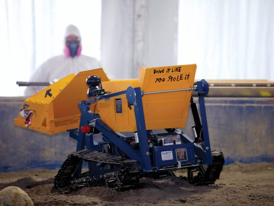 A robot miner traversed simulated Martian regolith in the mining area during NASA's 6th Annual Robotic Mining Competition in 2015 at the Kennedy Space Center Visitor Complex.