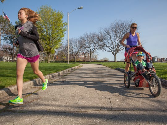 Indy Raymond (left), Emma Frappier and Grayson Tinkel (in stroller) run in Battery Park Wednesday.