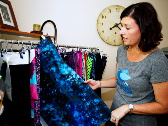 Alyson Neel looks through an assortment of fabrics at her home office in Fairview Tuesday. Her newly launched company, Blyss Running, was born out of frustration in trying to find running shorts or skirts that were long enough to prevent chaffing and also had pockets.
