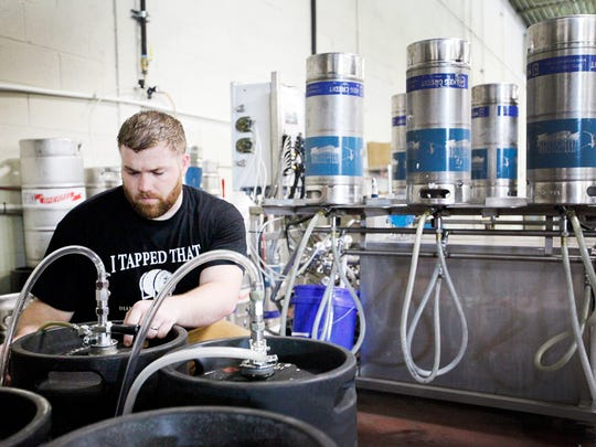 Dan Rowe, an A-B Tech intern, purges empty kegs returned from distributors at Hi-Wire Brewing's 2 Huntsman Place expansion June 23.