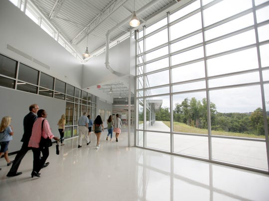 As Asheville City school officials, guests and a few students walk past a large wall of windows at the new Asheville Middle School August 19, 2016. The state-of-the-art school welcomes students August 29.