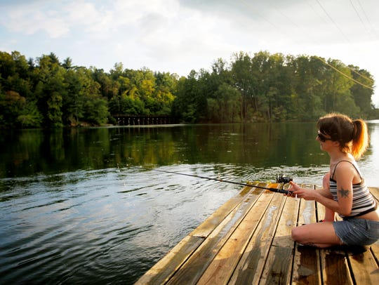Lois Revis fishes off a dock at Lake Julian in Arden