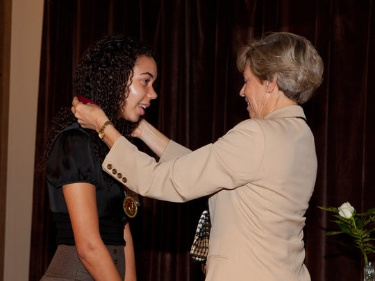 Kimora Williams, left, is presented the Garnet and Gold Scholar Society medal from Florida State University's Vice President for Student Affairs Mary Coburn.