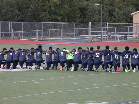 All 18 players for the World of Inquiry boys soccer team knelt during the anthem before a match at Aquinas Institute.