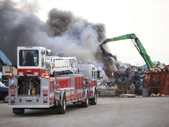 A crane moves scrap as crews work to put out a fire