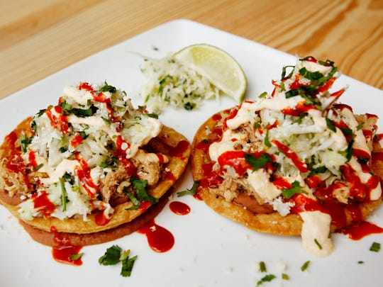 Sonora Cocina Mexicana's chicken tostada includes two fried corn tortillas with refried beans, chicken, cheese and cilantro lime slaw.