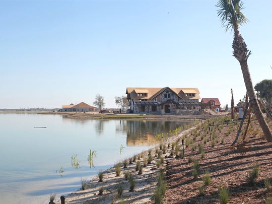 The clubhouse of Babcock Ranch's first neighborhood nears completion in the distance on Lake Timber,  a pit lake created by former mining activity across the Lee County line in Charlotte County.