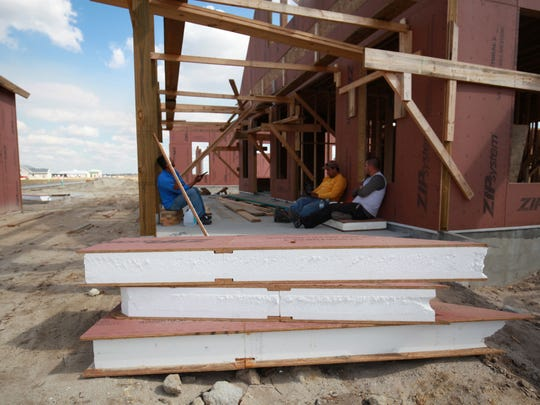 Workers take a break from installing the modular, insulated panels that form the energy efficient shell of several homes under construction at Babcock Ranch in Charlotte County on Thursday, February 2.