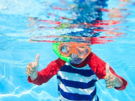 cute little boy swimming underwater