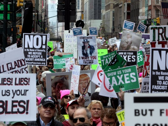 Thousands of protesters holds signs demanding that