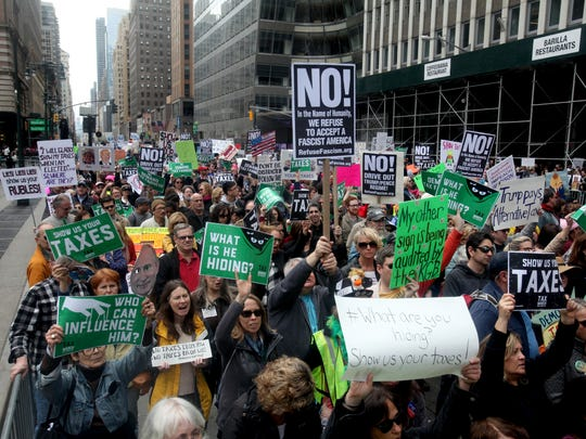 Thousands of protestors holds signs demanding that