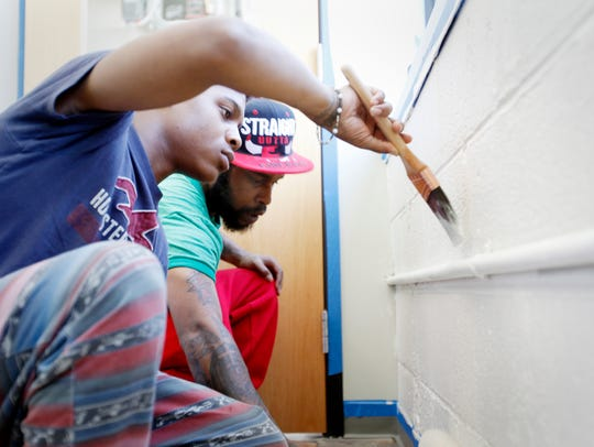 Tijaris Williams, left, and Chimarko Carson paint an