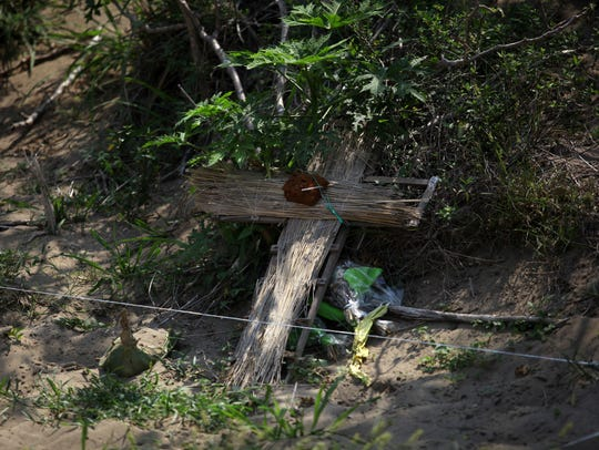 A makeshift cross marks a mass grave where the remains