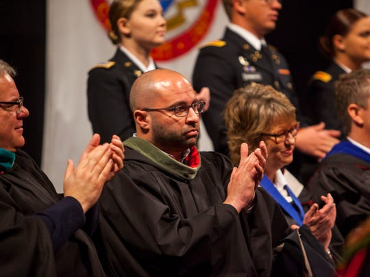 SUU athletic director Jason Butikofer applauds during Friday's commencement ceremony