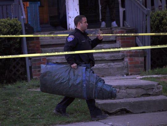 An officer leaving the crime scene on Dayton Street