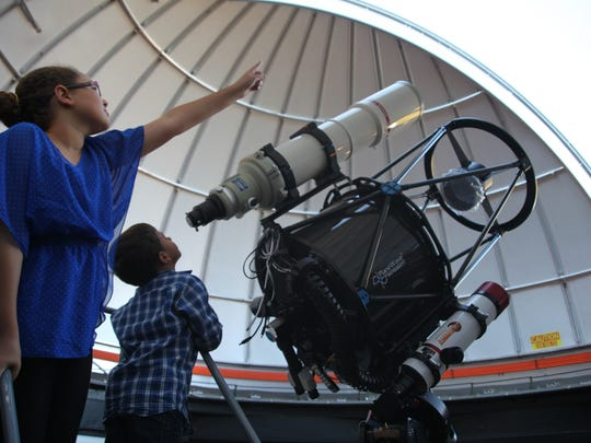 Haley Harding and Andrew Harding look through a telescope