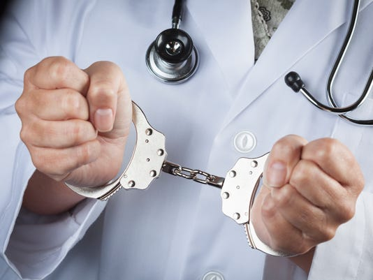 Female doctor in handcuffs wearing lab coat & stethoscope
